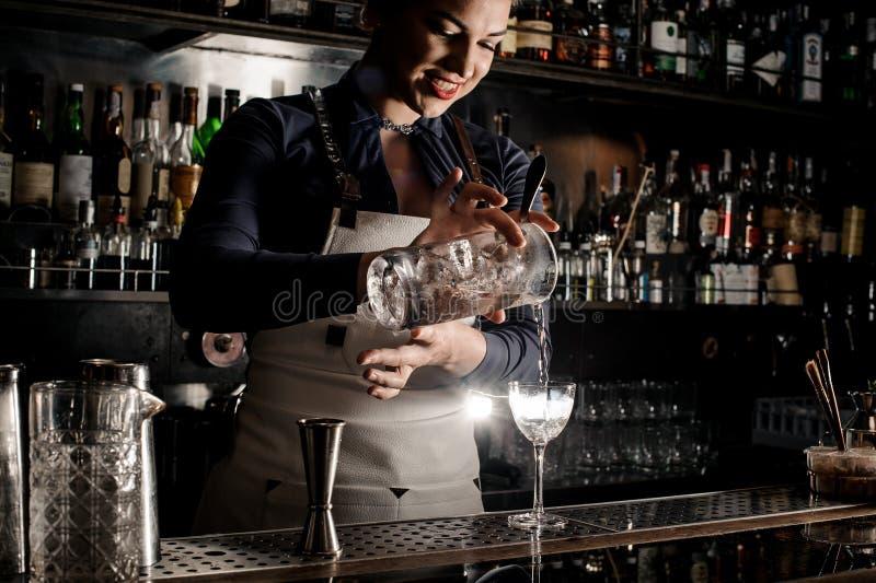Belle femme de sourire de barman versant le cocktail frais dans un gla images libres de droits