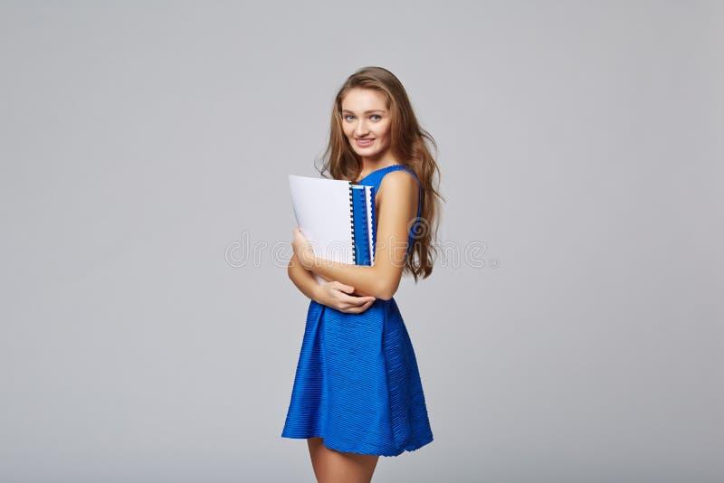 Belle femme de sourire d'affaires, avec des documents, sur un dos de gris photographie stock