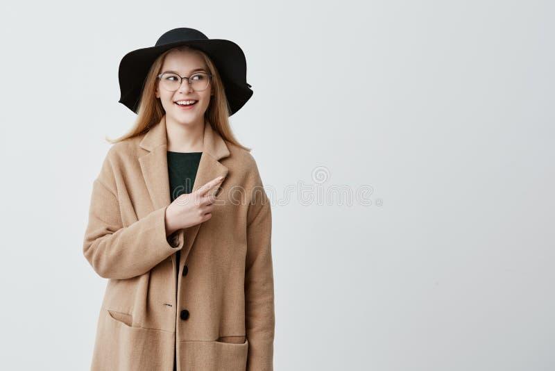 Belle femme de sourire dans le manteau au-dessus du chandail et des lunettes verts se dirigeant au mur blanc vide tout en démontr images libres de droits