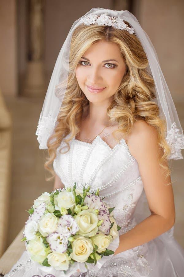 Belle femme de sourire de jeune mariée avec le bouquet des fleurs, épousant m images libres de droits