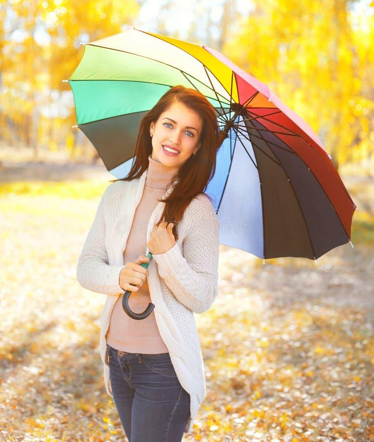 Belle femme de sourire de portrait avec le parapluie coloré en automne ensoleillé chaud photo libre de droits