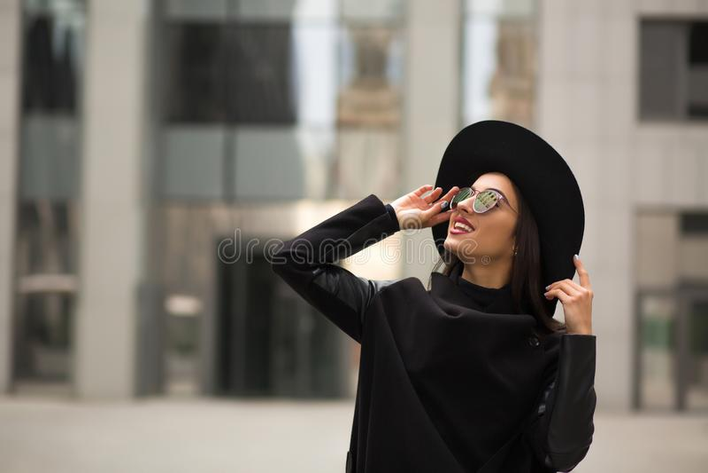 Belle femme de sourire en soleil au loin débordé de chapeau noir et de miroir image libre de droits