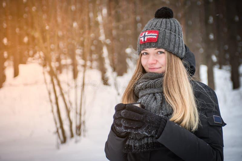 Belle femme de sourire heureuse avec une tasse de l'hiver sur la rue de sourire de plaisir de fille boisson chaude dehors images stock