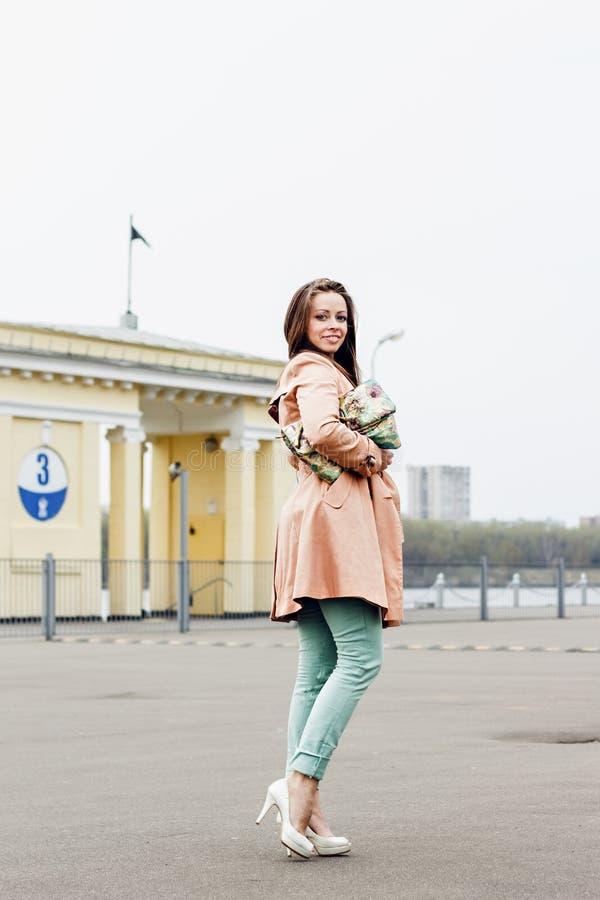 Belle femme de sourire heureuse dans l'équipement de mode sur le fond urbain photographie stock