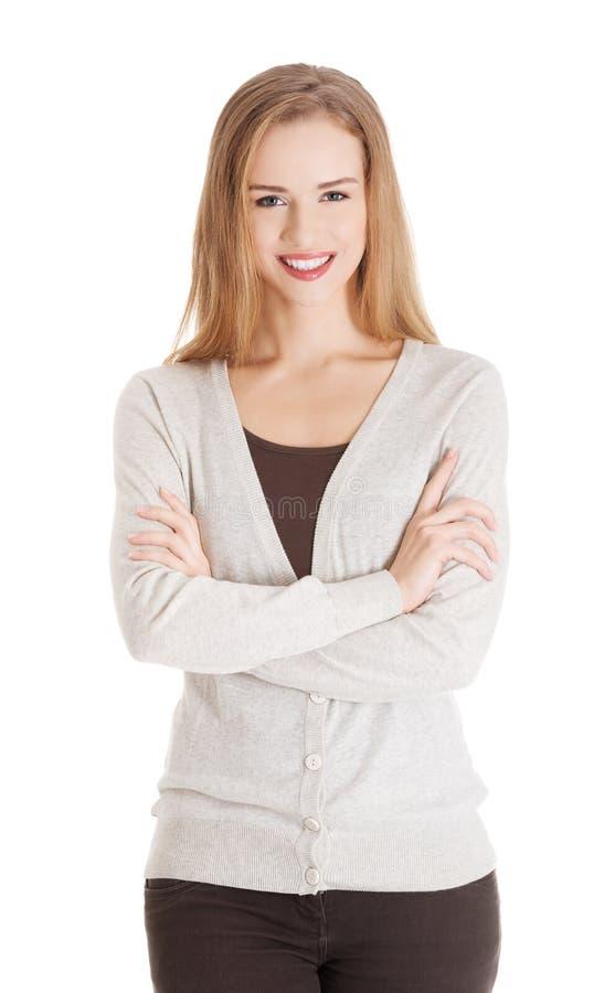 Belle femme de sourire occasionnelle avec les mains croisées. photographie stock libre de droits