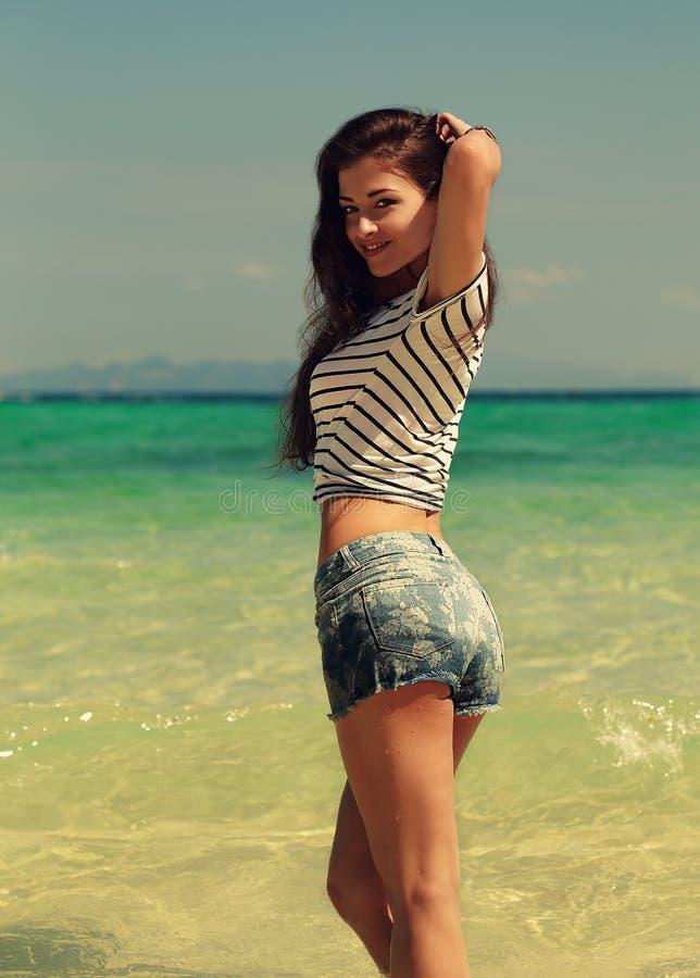 Belle femme de sourire posant sur le fond de mer dans des shorts bleus photo libre de droits