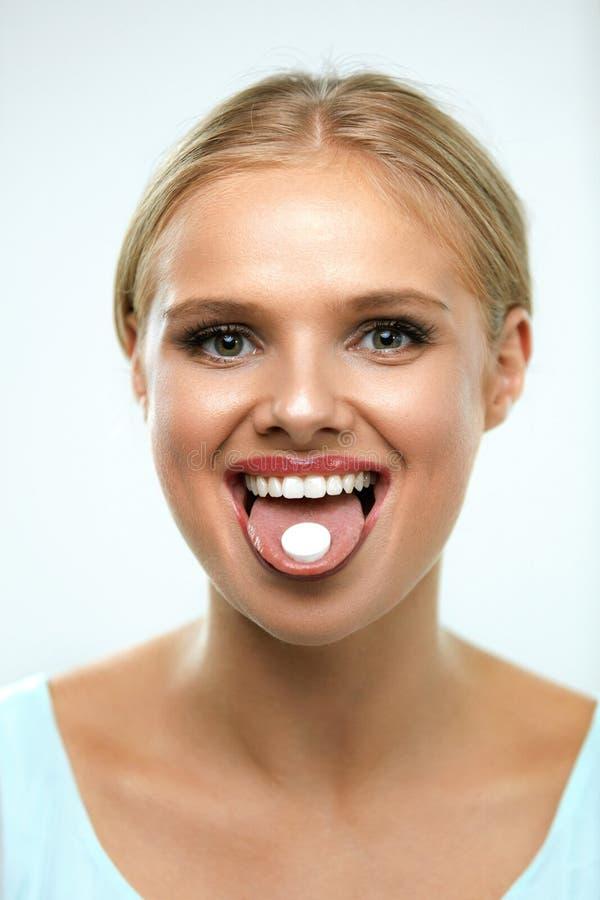 Belle femme de sourire prenant la médecine, tenant la pilule sur la langue photos libres de droits