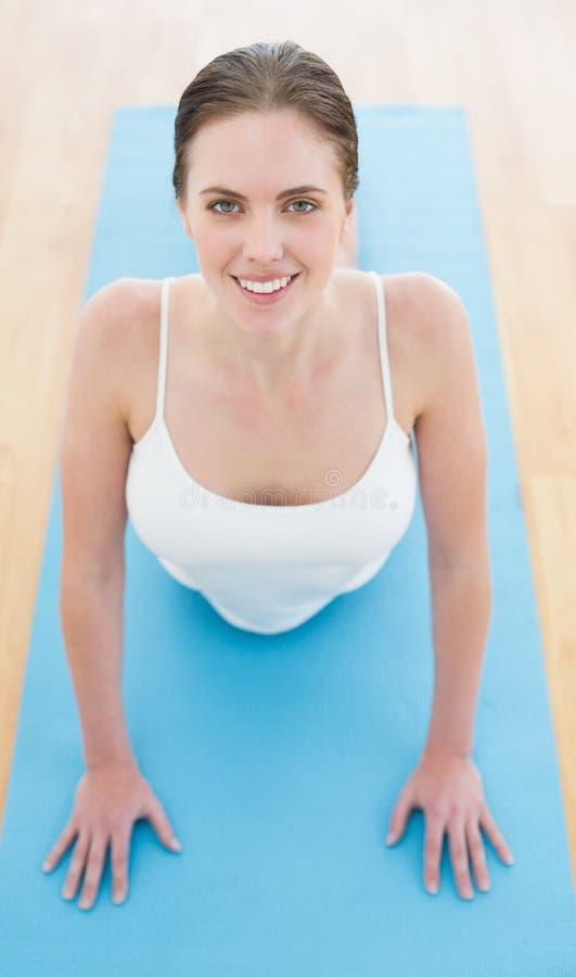 Belle femme de sourire s'étirant sur le tapis d'exercice images stock