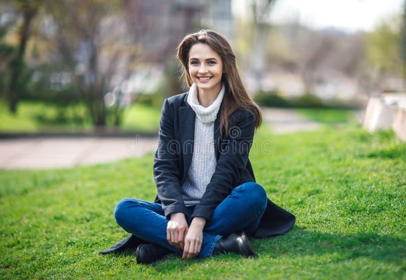 Belle femme de sourire s'asseyant sur une herbe extérieure photographie stock