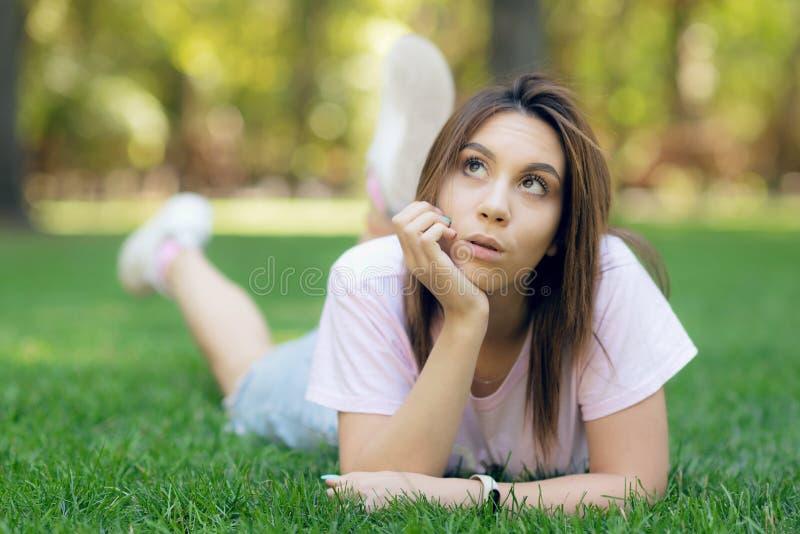 Belle femme de sourire se trouvant sur une herbe extérieure photographie stock