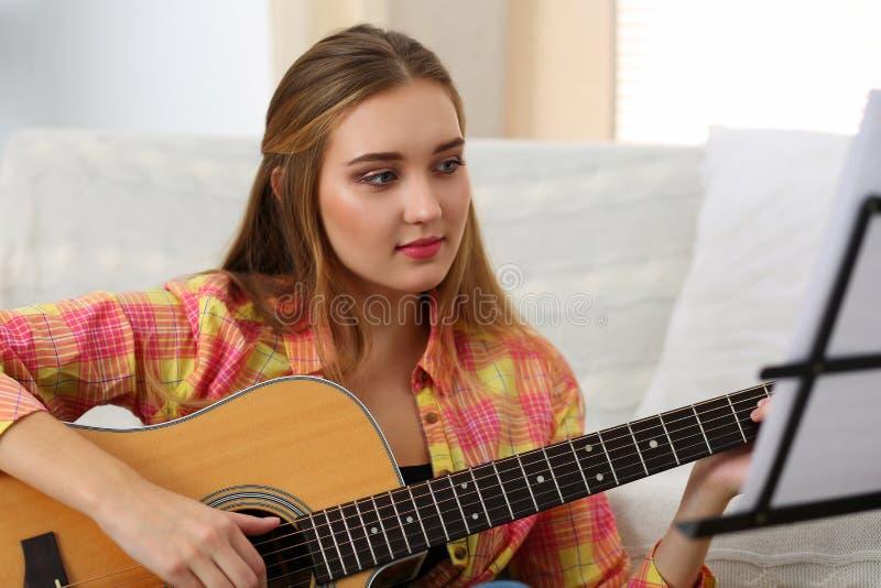 Belle femme de sourire tenant et jouant le GUI acoustique occidental image libre de droits