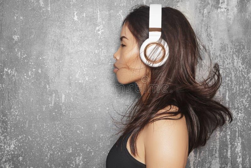 Belle femme de sport avec de grands écouteurs blancs Écoute modèle la musique Portrait de forme physique, formes parfaites de cor photos stock