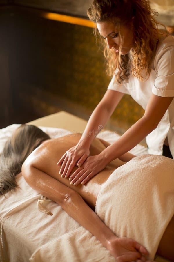 Belle femme de station thermale de brune obtenant le massage sur la serviette images stock