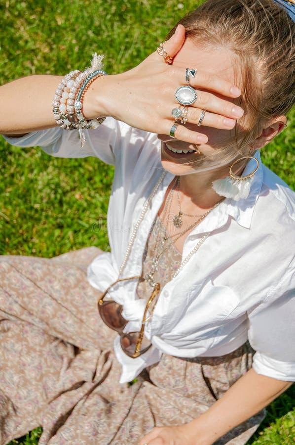 Belle femme de style de boho avec beaucoup d'accessoires, anneaux et bracelets sur l'herbe verte images stock