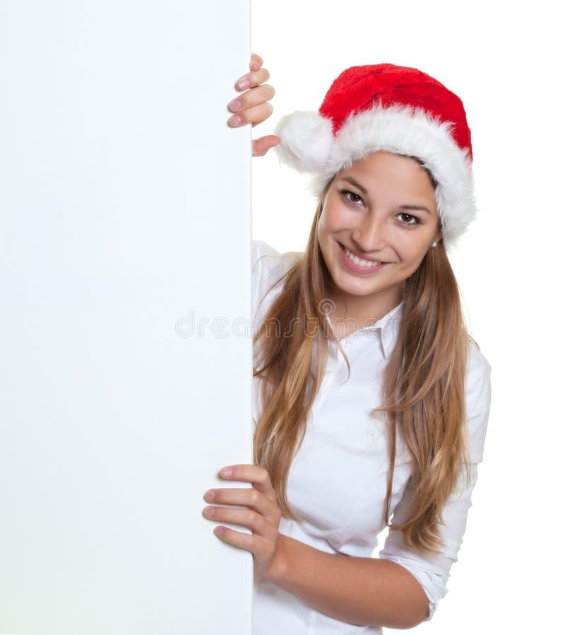 Belle femme derrière une enseigne riant de l'appareil-photo photographie stock