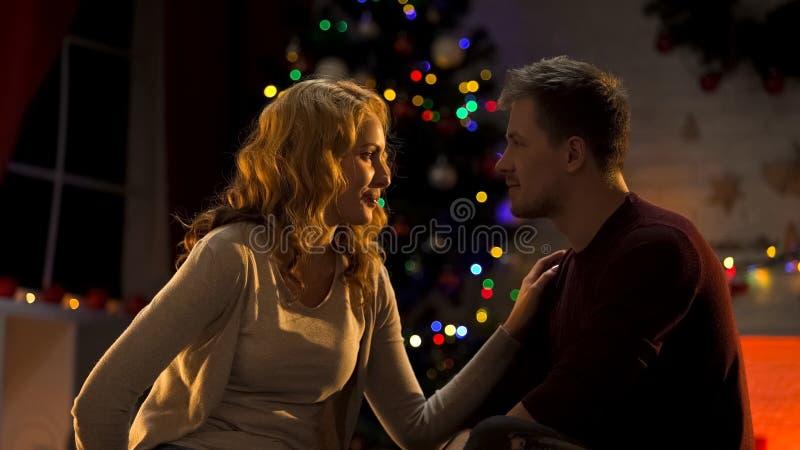 Belle femme disant à son ami de grandes nouvelles le réveillon de Noël, surprise image stock