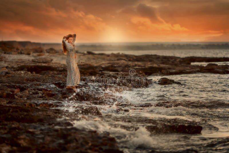 Belle femme en bord de la mer de roches au lever de soleil images libres de droits