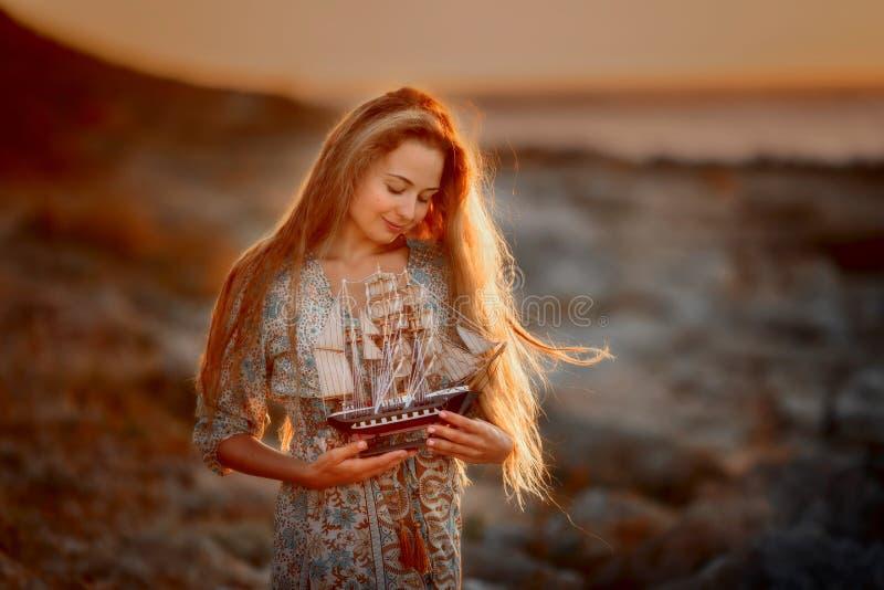 Belle femme en bord de la mer de roches au lever de soleil image libre de droits