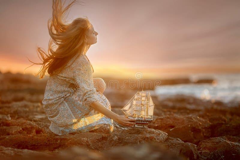 Belle femme en bord de la mer de roches au lever de soleil photos libres de droits