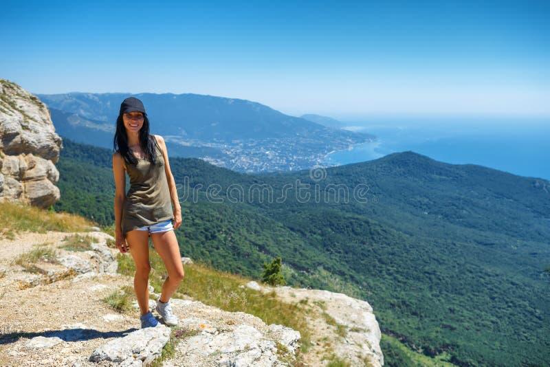 Belle femme en bref se tenant sur une falaise avec une belle vue, le concept du tourisme et le voyage photographie stock libre de droits
