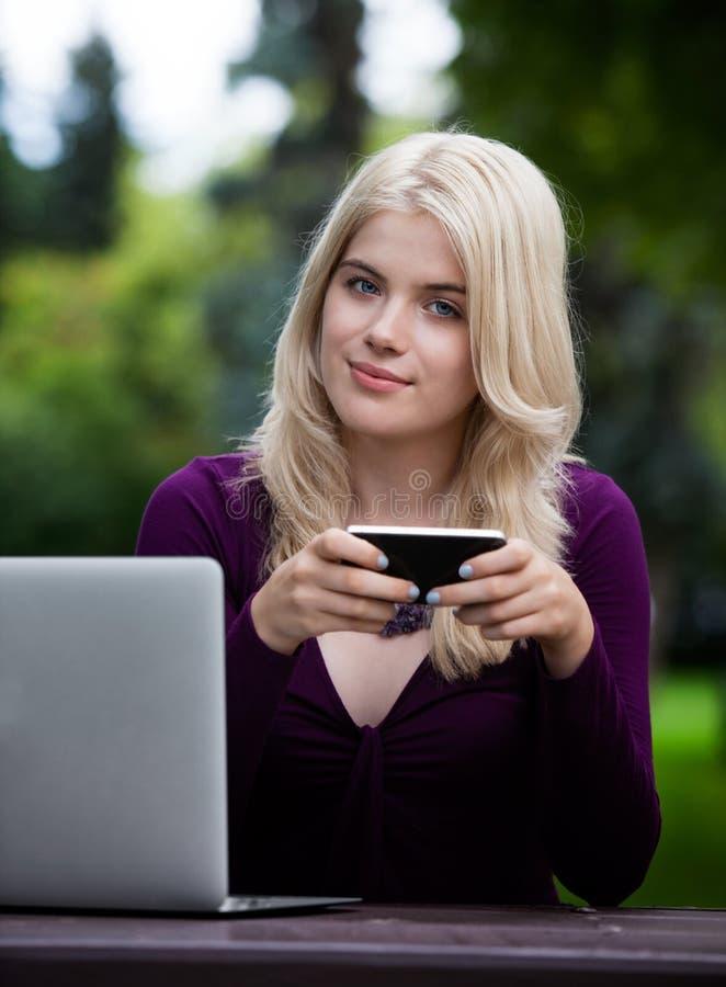 Belle femme en parc avec le téléphone intelligent image stock