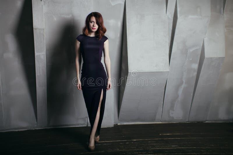 Belle femme en portrait gris de mode de fond de longue robe foncée images stock