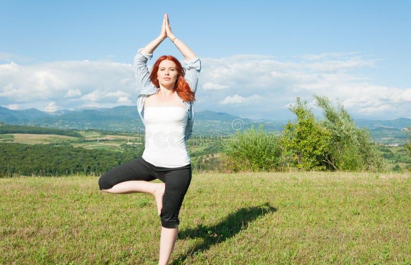 Belle femme en position de yoga d'arbre photo stock