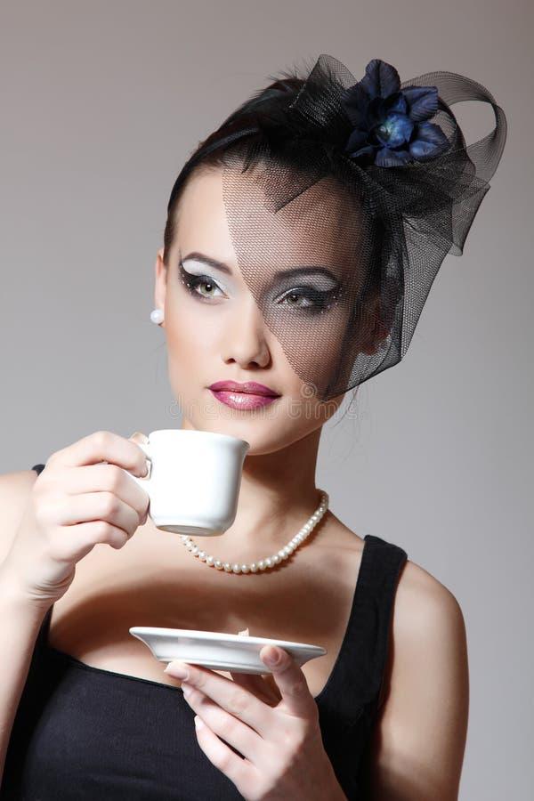 Belle femme en rétro portrait de charme de voile avec la tasse de thé o photo libre de droits