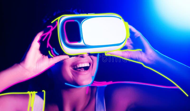 Belle femme en verres du vr 3d, fond coloré lumineux photo libre de droits