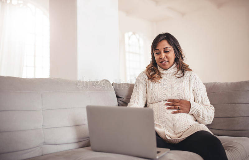 Belle femme enceinte avec l'ordinateur portable se reposant sur le sofa image stock