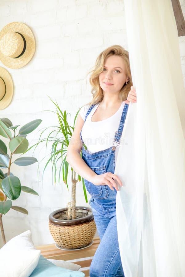 Belle femme enceinte avec les cheveux blonds dans un T-shirt blanc et des blues-jean dans une chambre avec un bon nombre de vivre images stock