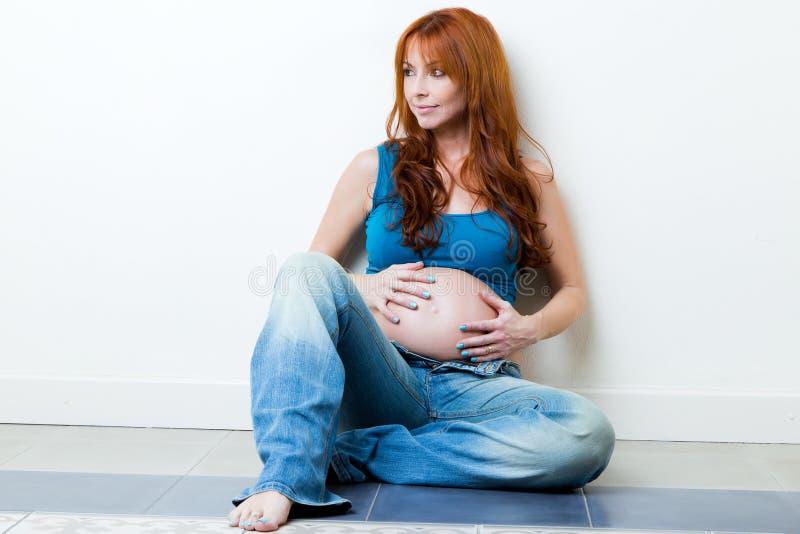 Belle femme enceinte détendant à la maison image stock