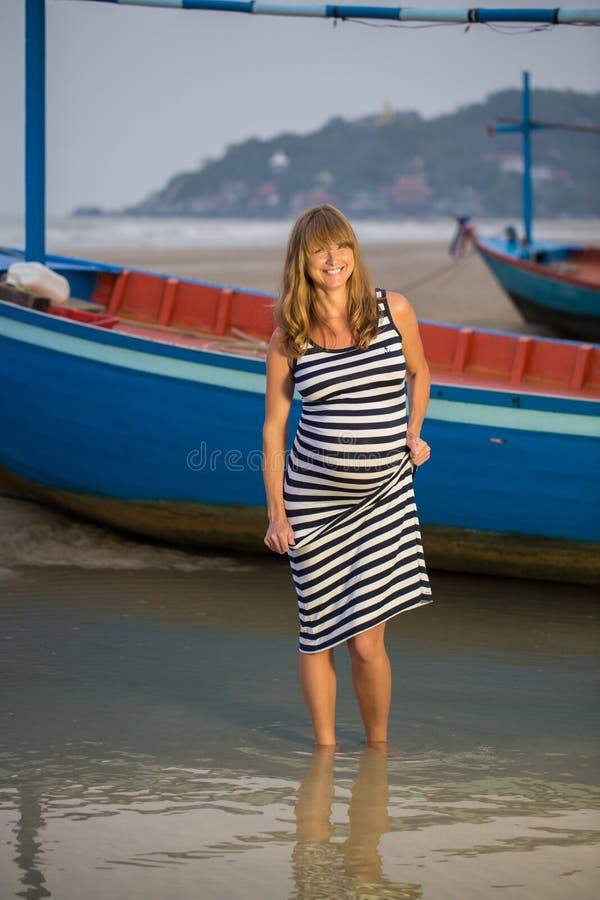 Belle femme enceinte détendant sur une plage photos libres de droits