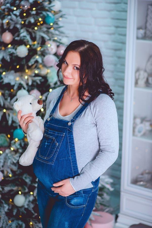 Belle femme enceinte dans des combinaisons de denim tenant un ours de nounours images stock