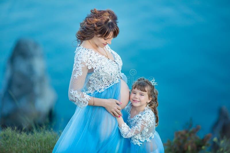 Belle femme enceinte dans la robe volante romantique en mer avec la fille près des ruines antiques de fille enceinte magnifique d photo libre de droits