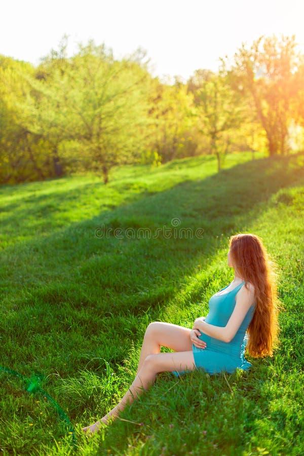 Belle femme enceinte dans le jardin coucher du soleil ou lever de soleil photos libres de droits