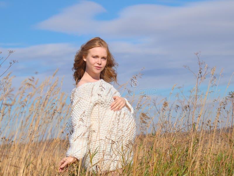 Belle femme enceinte dans un chandail de laine blanc photographie stock libre de droits