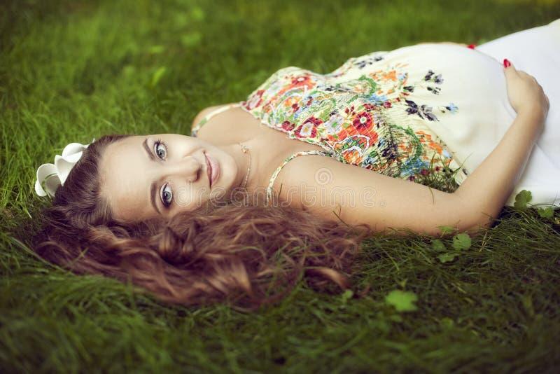 Belle femme enceinte européenne dans un bain de soleil floral au su images stock