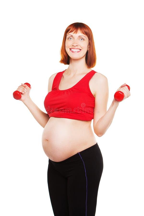 Belle femme enceinte faisant l'exercice avec photographie stock