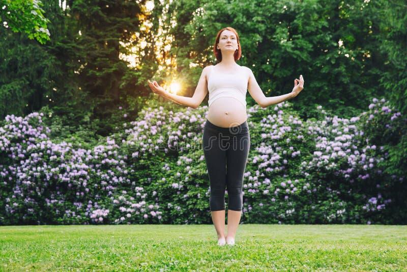 Belle femme enceinte faisant le yoga prénatal sur la nature dehors image libre de droits