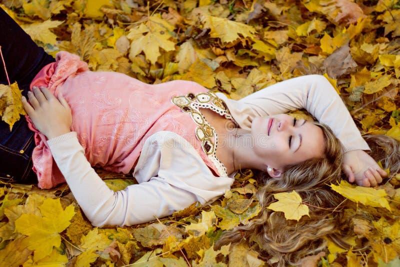 Belle femme enceinte heureuse se trouvant avec des feuilles d'automne photo stock