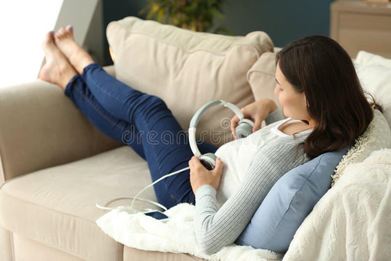 Belle femme enceinte mettant des écouteurs sur le ventre tout en se reposant à la maison photos stock