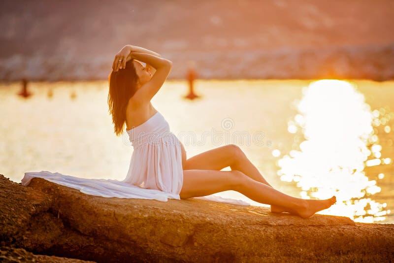 Belle femme enceinte, s'asseyant sur le rivage sur la plage sur s photos libres de droits
