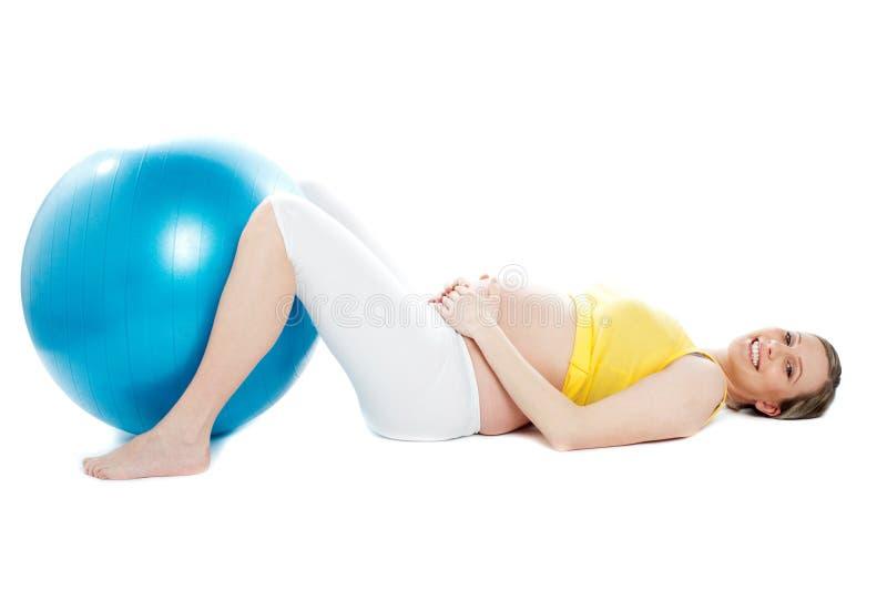 Belle femme enceinte se trouvant avec la bille d'exercice photos libres de droits