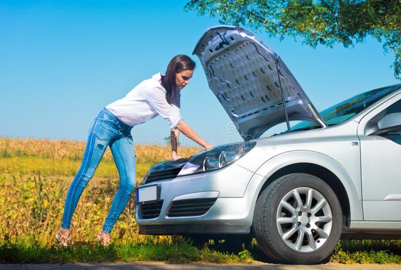 Belle femme essayant de réparer une voiture cassée photographie stock libre de droits
