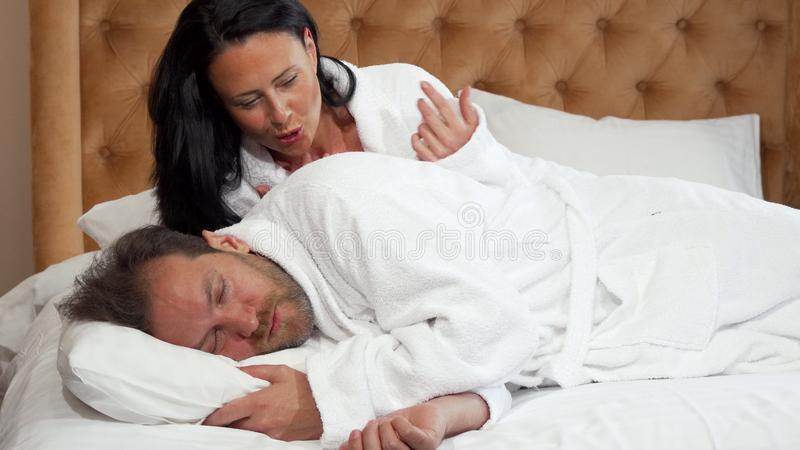 Belle femme essayant réveillant son mari de sommeil images stock