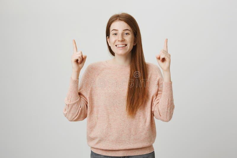 Belle femme européenne rousse positive se dirigeant avec des index tout en souriant largement et jetant un coup d'oeil sur l'appa photo stock