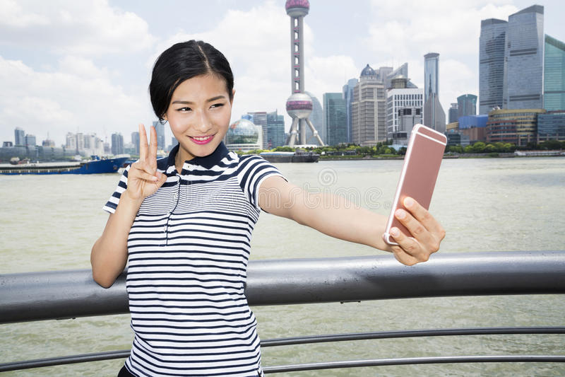 Belle femme faisant des gestes le signe de paix tout en prenant le selfie par le téléphone intelligent contre l'horizon de Pudong image libre de droits