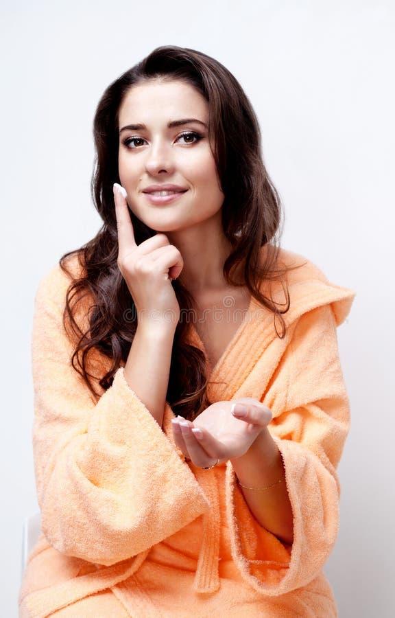 Belle femme faisant des soins de la peau avec de la crème photographie stock libre de droits