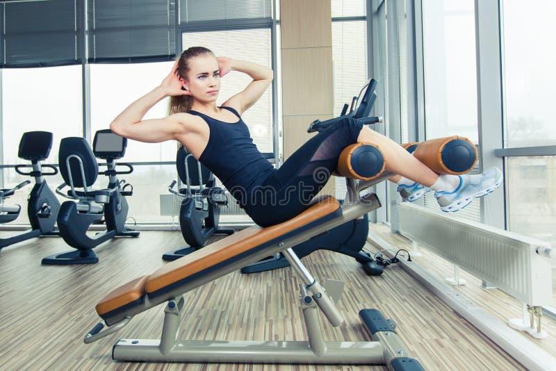 Belle femme faisant l'exercice de forme physique de presse au gymnase de sport image libre de droits
